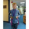 Eli with his medals from the past 3 years.