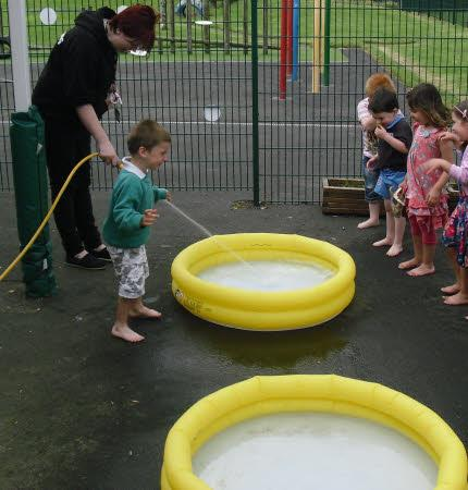 Miss Herbert gets the paddling pools ready