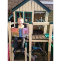 Robbie reading in the playhouse at Grandmas
