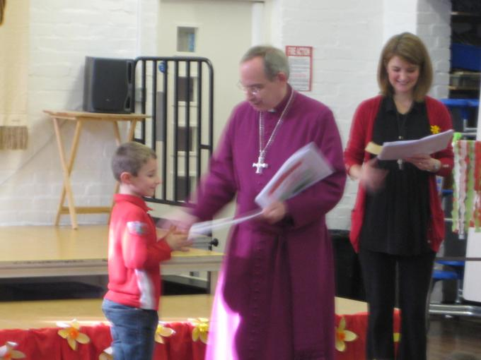 Bishop Richard hands out some certificates.