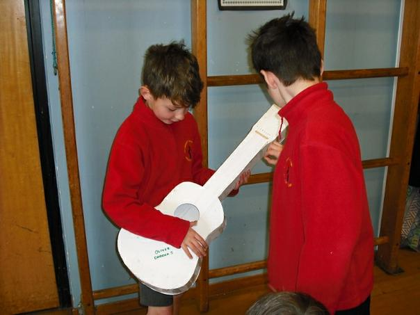 Demonstrating a homemade string instrument.