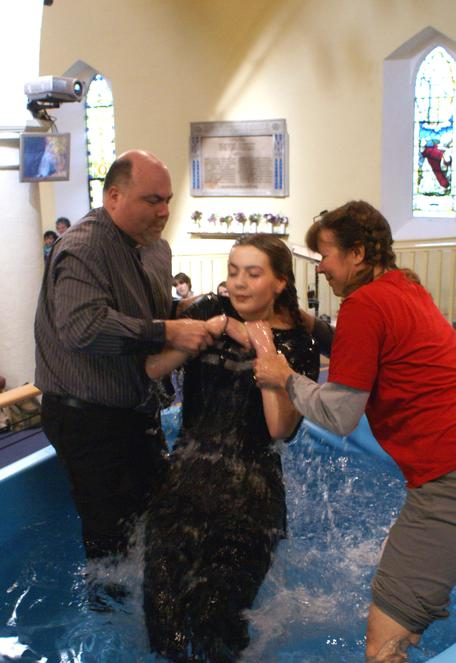 A young woman being Baptised by Full Emersion