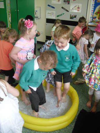 having great fun playing in the paddling pool!