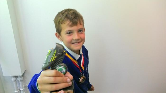 Ethan shows off his football trophy and Pace medal