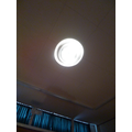 Looking at the light on the ceiling.