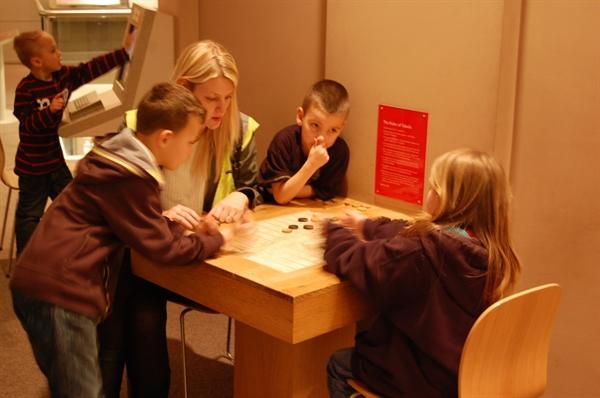 Playing a Roman game like drafts at the museum.