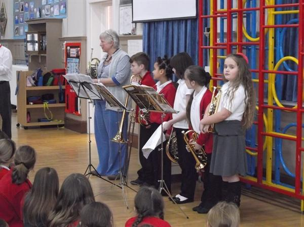 Brass players play in assembly