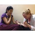 Applying mehndi designs with henna.