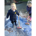 Using brooms to mix powder paints in to a puddle.