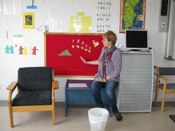 Teacher Gunilla uses pictures to teach songs