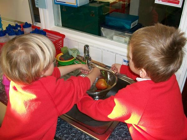 Making fruit kebabs. First we washed the fruit.
