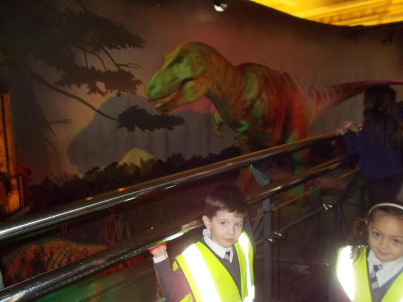 Tom and Charlotte stand bravely by the T.rex