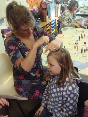 Luke's mum helps on the hair stall.