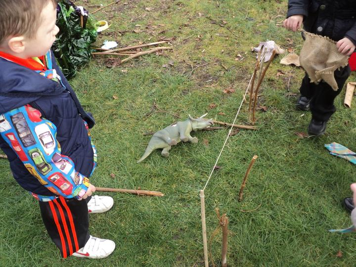 Building homes for the dinosaurs using sticks.