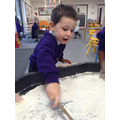 Using a stick to write in flour.
