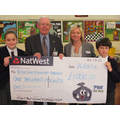Emily and Nathan handing over the cheque