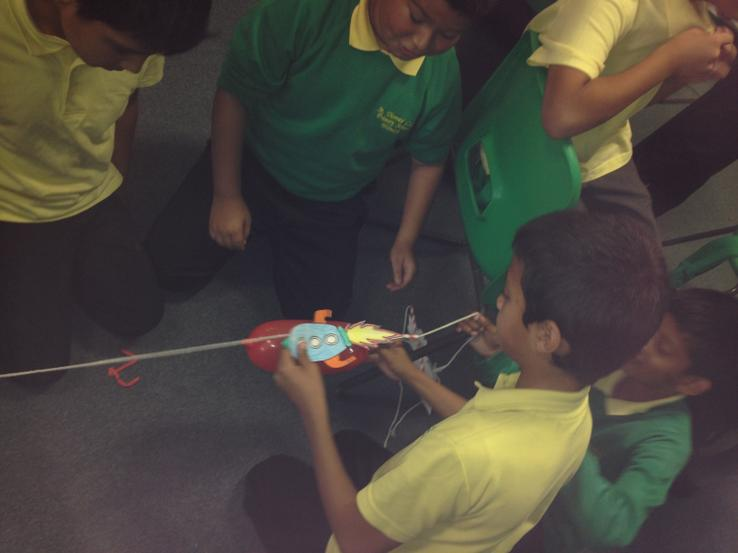 Using a card rocket and a balloon.