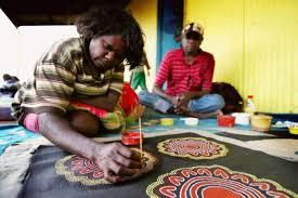 Aboriginal man creating a large piece of art work.